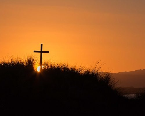Cross on a tusket hill as the sun rises for anther day